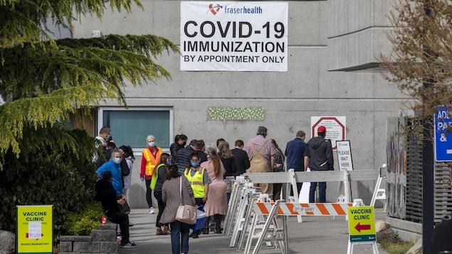 Des gens attendent en ligne devant une clinique de vaccination à Cloverdale.