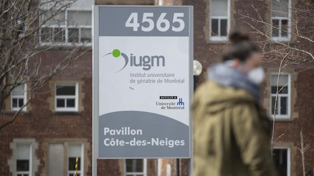 Une personne masqué marche devant l'Institut universitaire de gériatrie de Montréal.
