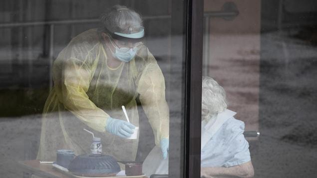 Une préposée portant un équipement de protection en train d'aider une patiente dans un CHSLD.
