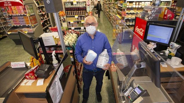 Franck Henot est debout entre deux caisses et tient dans ses mains des masques de procédure et une bouteille de désinfectant.