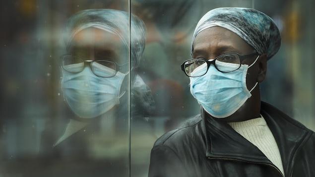 Une femme qui porte un masque attend dans un arrêt d'autobus.
