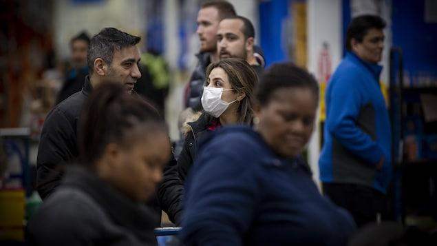 Des personnes dans une foule, une femme porte un masque.