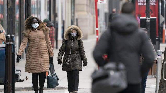 Des gens marchent sur un trottoir de la ville.