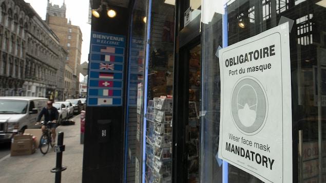 Une affiche indiquant que le port du masque est obligatoire collée sur la vitrine d'un commerce de Montréal.