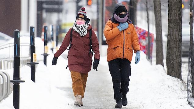 Deux personnes habillées chaudement marchent sur le trottoir avec un masque.