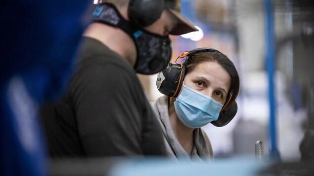 Des gens portent un masque.