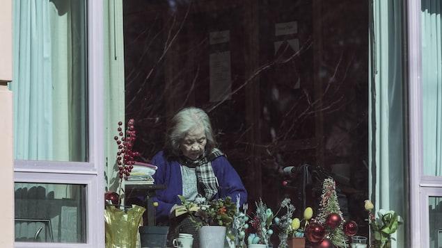 Une personne est photographiée derrière une fenêtre au centre de soins longue durée Lynn Valley à North Vancouver, en Colombie-Britannique, le lundi 9 mars 2020.