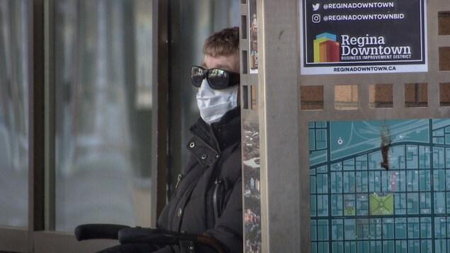 Une personne, appuyée sur un mur, avec un masque sur la bouche et sur le nez.