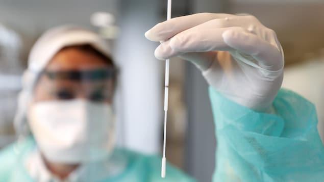 Une technicienne de laboratoire tient un écouvillon dans sa main.
