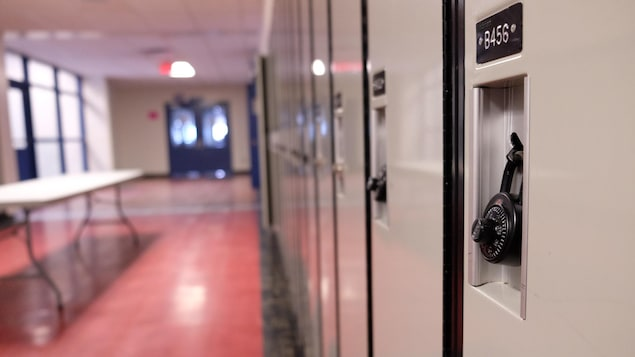 Un gros plan sur les casiers, avec les cadenas sur les portes, dans un corridor vide.