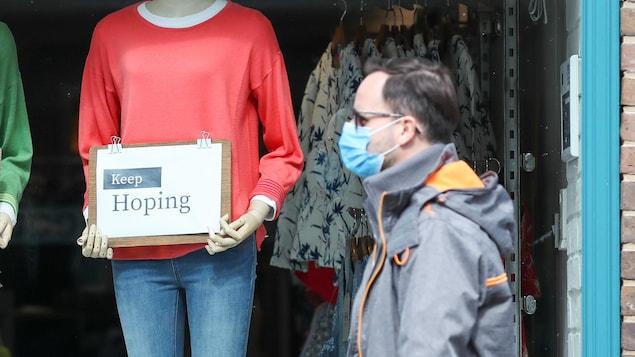 Un homme passe devant la vitrine d'un magasin fermé où deux mannequins tiennent des écriteaux sur lesquels on peut lire « Keep Hoping ».