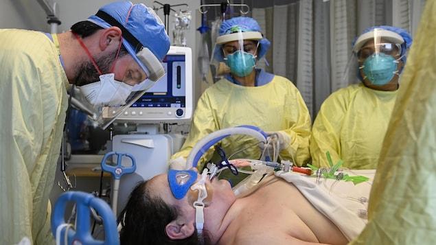 Une femme intubée entourée de personnel médical.