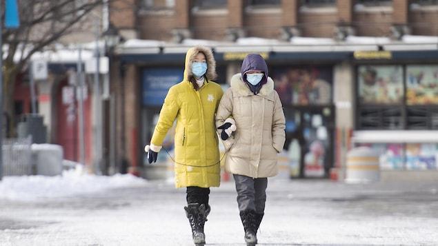 Deux femmes marchent dans la rue.
