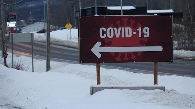 Une pancarte COVID-19 rouge avec de la neige et une route déserte en arrière-plan.
