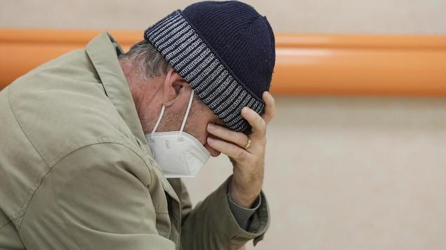 Un homme vu de profil portant un masque sur la bouche et coiffé d'une tuque est assis et se tient la tête avec une main.