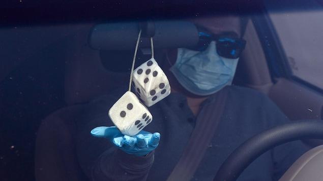 Un homme portant un masque, des lunettes fumées et des gants bleus en latex est dans sa voiture. Il touche les dés en peluche accrochés au rétroviseur intérieur de son véhicule.