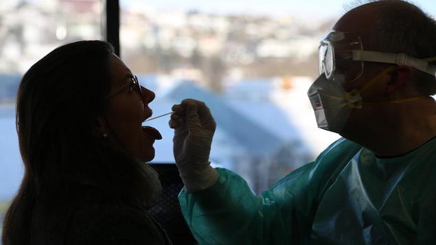 Une femme subit un test de dépistage de la COVID-19 à Reykjavik, en Islande.