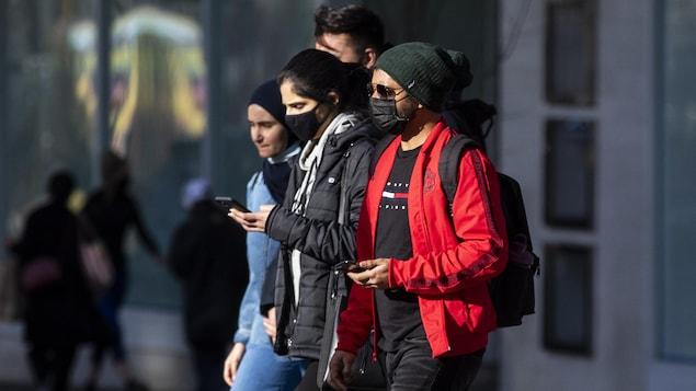 De jeunes adultes marchent dans les rues à Vancouver.