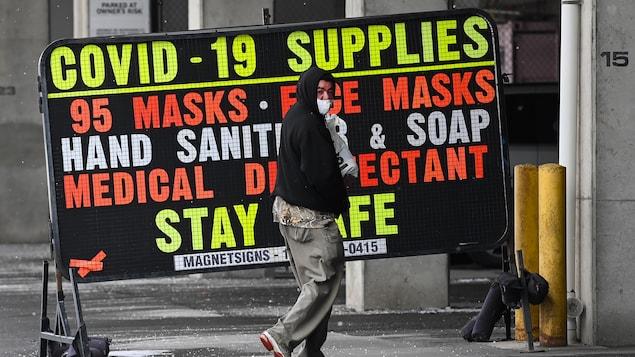 Un homme marche devant l'affiche d'un magasin qui vend des fournitures contre la COVID-19.