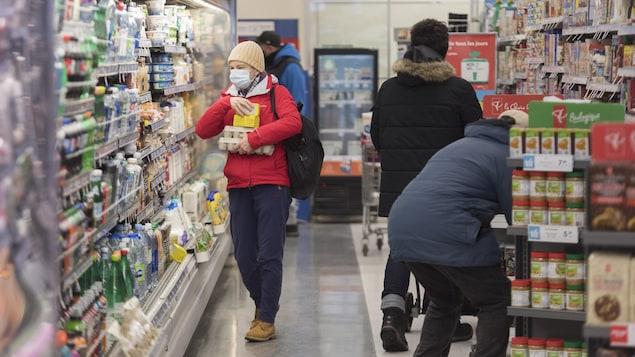 Des gens font leurs achats dans une épicerie.