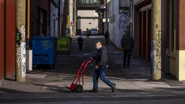 Un homme marche dans une rue de Vancouver.