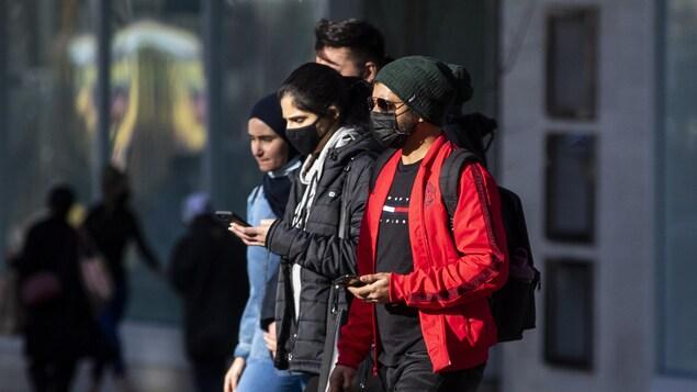 Des gens portant des masques marchent le long de la rue Granville, à Vancouver.