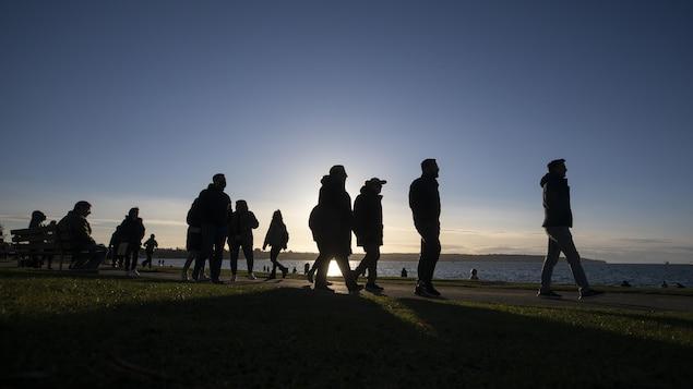 Des gens qui marchent au bord de l'eau à Vancouver.