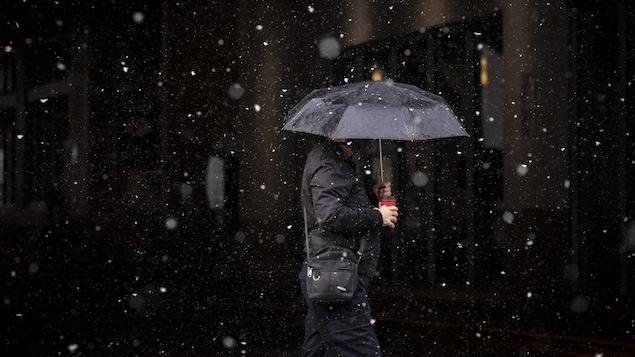 Un homme marche sous la pluie.