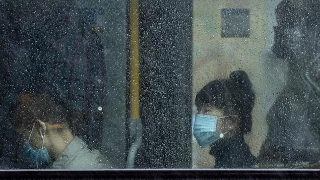 Des usagers du transport en commun portent un masque.