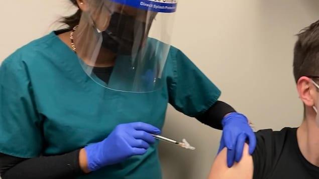 Un bénévole se fait injecter une dose du vaccin à l'essai.