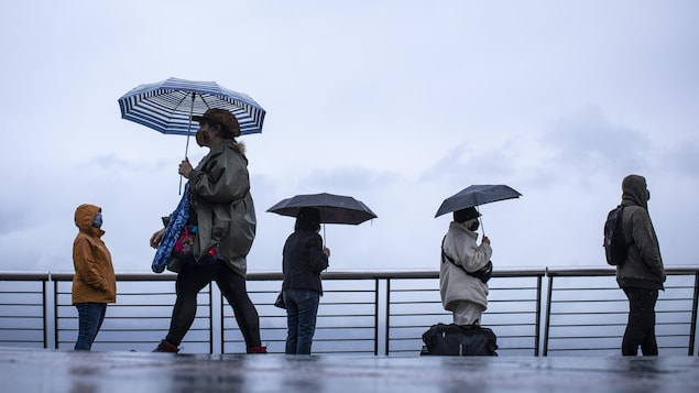 Des gens font la file sous la pluie.