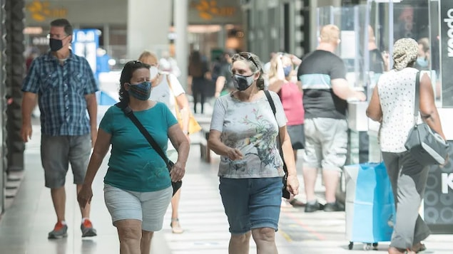 People wear face masks as they walk through a shopping mall in Montreal last summer. Businesses hope that consumers will flood back this summer, too, as COVID-19-related restrictions ease.