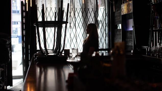 Une femme dans un bar sombre.
