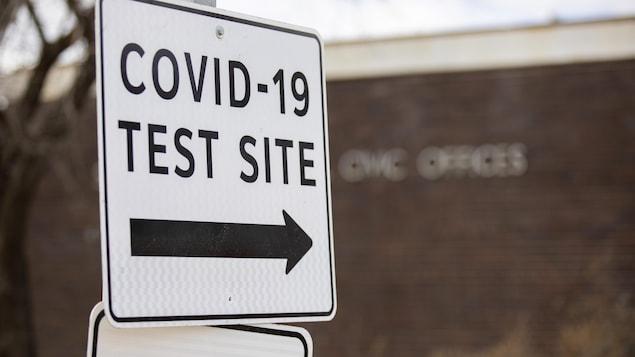 Une affiche indique par une flèche l'entrée d'un centre communautaire pour les tests de dépistage de la Covid-19.