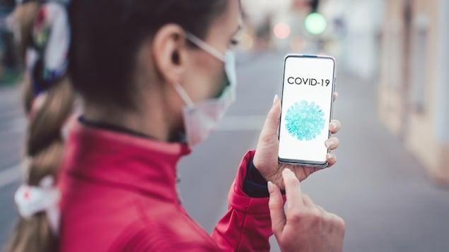 Une femme portant un masque chirurgical regarde son téléphone sur lequel il est écrit COVID-19.