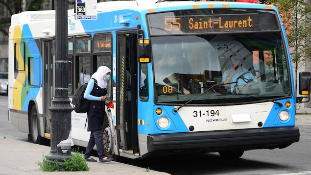 Une femme portant un masque s'apprête à monter dans un autobus.