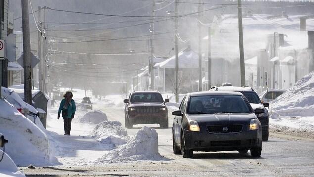 Une dame marche sur le trottoir d'une rue à côté de voitures qui circulent sur la voie.