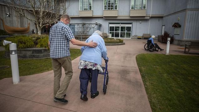 Un homme accompagne sa mère qui marche à l'aide d'un déambulateur à l'extérieur du centre de soins Normanna à Burnaby.