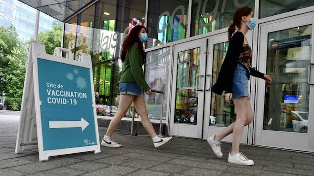 Deux femmes marchant masquées vers un site de vaccination.