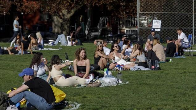 Des groupes de personnes assis dans des cercles de distanciation au parc Trinity Bellwoods.