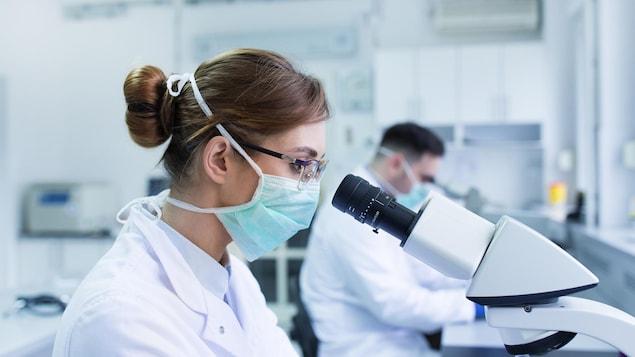 Une biologiste regarde dans un microscope.