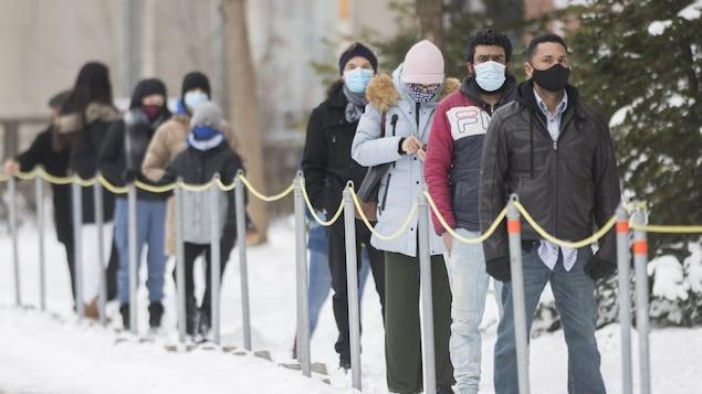 Une file de personnes portant un masque qui attendent dehors.