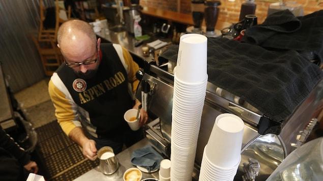 Un employé dans le commerce Le Pourquoi pas espresso-bar prépare un café.
