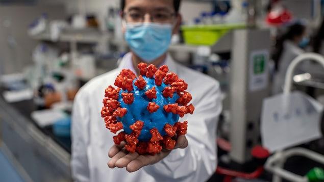 Représentation d'une molécule du coronavirus dans la main d'un infirmier.