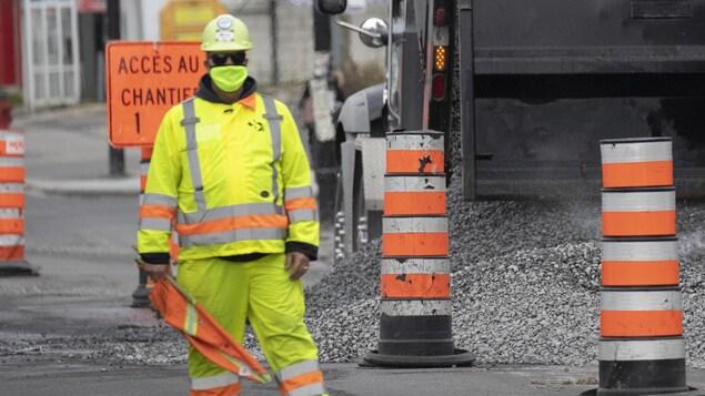 Un homme habillé tout en jaune et portant un masque se tient près d'un camion qui déverse du gravier.