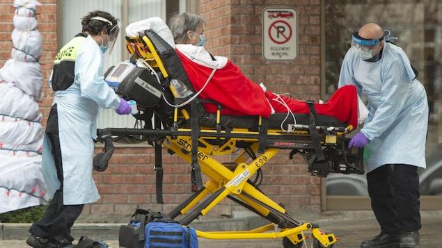 Une patiente aînée transportée sur une civière par des ambulanciers.