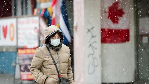 Une femme sur le trottoir, sous la neige