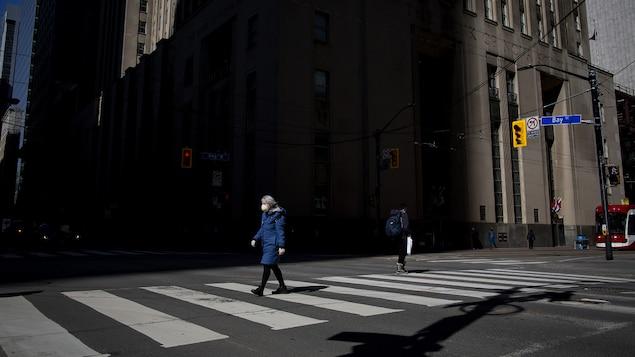 Une femme portant un masque de protection marche travers une rue du centre-ville de Toronto.