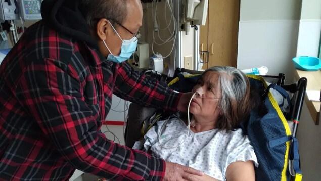 Un homme masqué prend soin de son épouse hospitalisée à cause de la COVID-19.