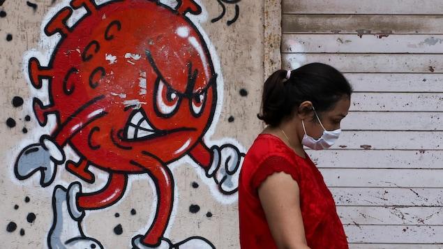 Une femme portant un masque marche devant un graffiti d'un virus menaçant.